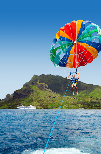 Moorea_parasail - A Paul Gauguin guest experiences Moorea's coastal beauty in a thrilling new way during a memorable parasailing adventure.