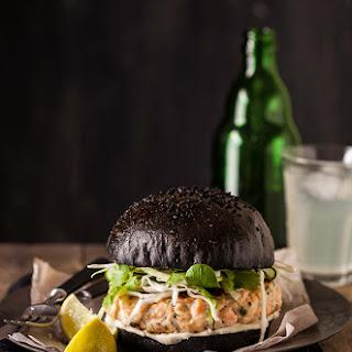 Salmon Burger On A Black Brioche Bun.