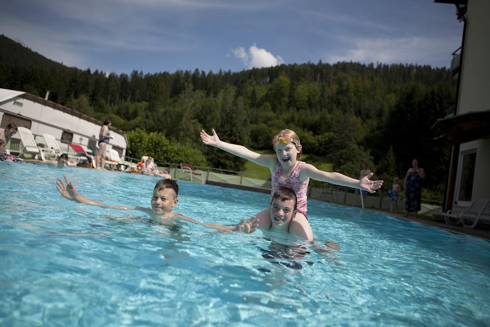 Du siehst spielende Kinder bei sonnigem Wetter in einem Pool
