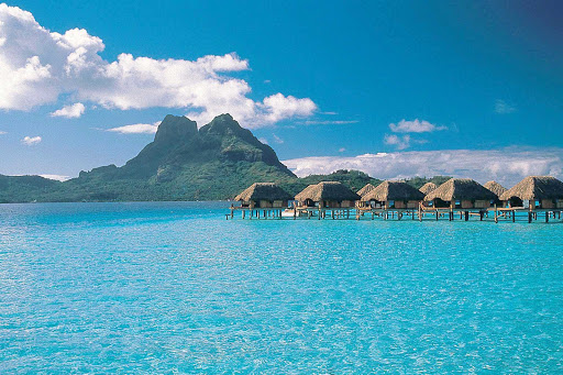 The aquamarine lagoon and bungalows at the Bora Bora Pearl Beach Resort. Some cruise guests come for a day visit, others do an overnight or longer stay.