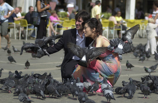 JFvenice-weddingcouple - Wedding couple overwhelmed by fowl in St. Mark's Square.