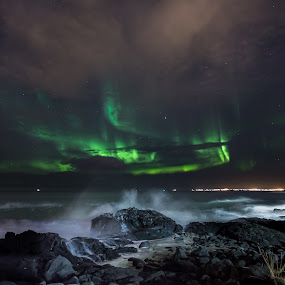 Northern Lights on a Rocky Beach by Sigurður Brynjarsson - Landscapes Waterscapes ( water, shore, sand, bright, aurora, star, land, stone, sea, rock, shine, ocean, city, northern, iceland, sky, borealis, reykjavik, wave, cloud, night, light, crash )