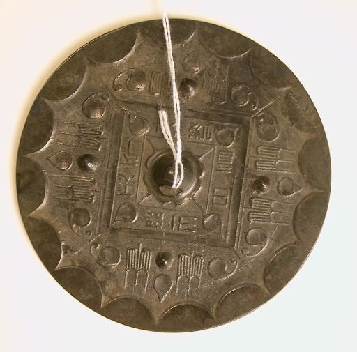 Inscribed round mirror with vegetal and lobed decoration