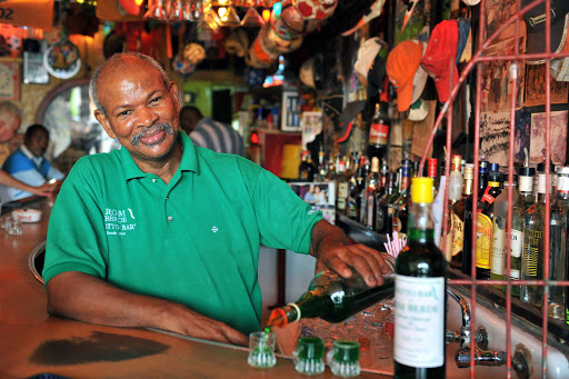 "Curacao-Netto-Bar - Jesus M.E ""Chu"" Zimmerman, proprietor of the Notto Bar in Willemstad, Curacao, pours shots of the famous Ròm Bèrdè, a house-made green rum."