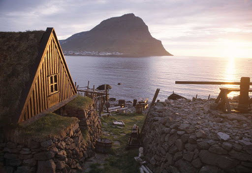A traditional turf house by the sea at sunset in Iceland.