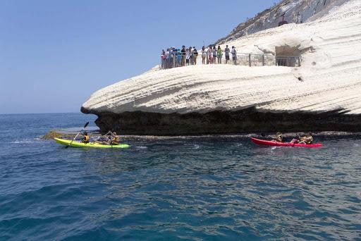 Kayakers paddle by Rosh Hanikra, Israel.