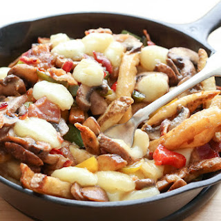 Montreal-Style Poutine with Bacon, Peppers, Mushrooms, and Onions.
