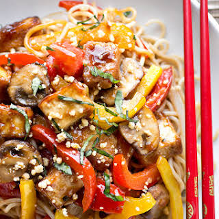 Thai-Style Crispy Tofu Sauteed with Red and Yellow Bell Peppers, Onions, Mushrooms and Tomatoes with Fresh Basil and Crushed Peanuts Over Brown Rice Noodles.