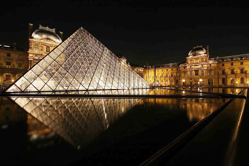louvre-paris-france-1 - The Louvre and its iconic pyramid at night in Paris.