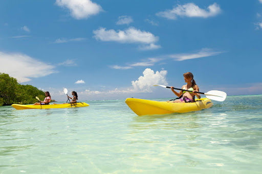 Friends come together to take a kayak tour in the tropical waters of Aruba.