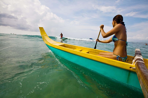 Hawaii-canoe - A young Hawaiian woman paddles an outrigger canoe. Hawaii is a mecca for water sports.