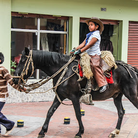 Boy on horse  walking down the street in the small town of Cotac by Judith Dueck - People Street & Candids ( reins, ecuador, mane, cotacachi, street, horse, lead, road, main street, hooves, andes, village, riding, saddle, south america, town, proud, indigenous, boy, leather, black )