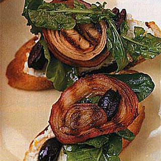 Grilled Bread Topped with Arugula, Goat Cheese, Olives and Onions.