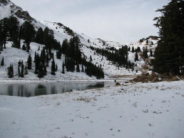 A frozen lake a short way below a ridgeline.