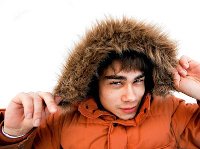 image shows Alexander Rybak smiling at the camera, wearing a big eskimo style hood on a bright orange coat
