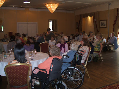shot of many people, some old, some in wheelchairs, at hotel tables all looking at a stage