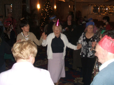 A group of old people dressed in party hats in a circle up for a dance in a big room. Loads of people up dancing