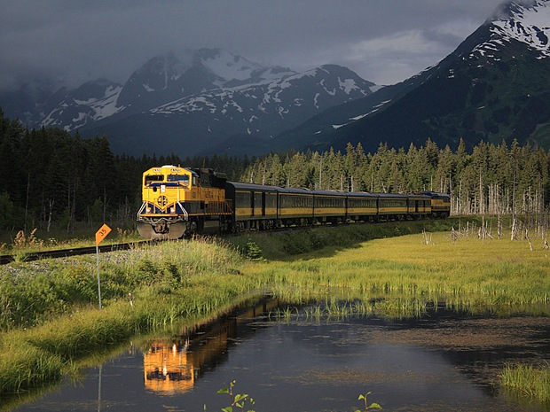 Passenger train passes through Girdwood Valley in Alaska, USA. Dark storm clouds are shrouding the Chugach Mountains as the train finds a bit of sun to cast it's reflection in the saline ponds.