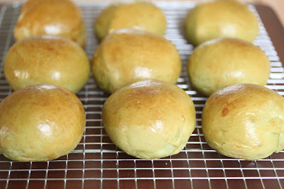 freshly baked match bread rolls cooling on a wire rack