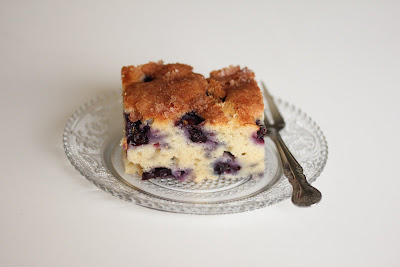 photo of a slice of blueberry cake on a plate with a fork