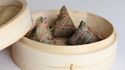 photo of three Rice dumplings in a bamboo steamer