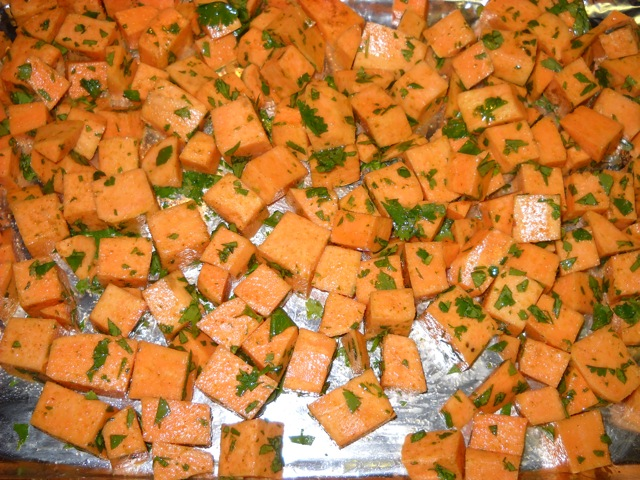 sweet potatoes tossed with olive oil, cumin, cilantro and salt on baking sheet
