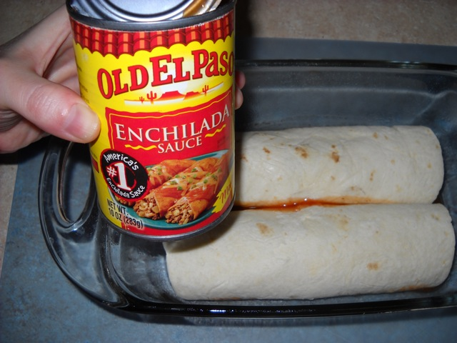 rolled enchiladas placed in baking pan with enchilada sauce to be poured on top