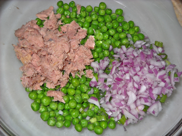 Tuna, peas and onions in clear mixing bowl