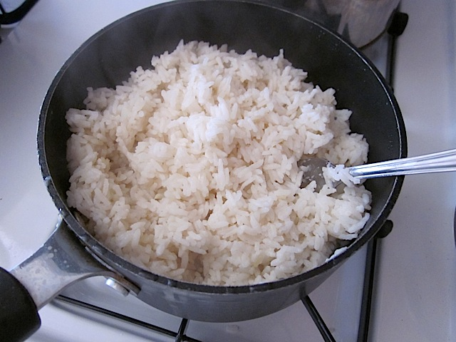 cooked rice in pan with fork to fluff