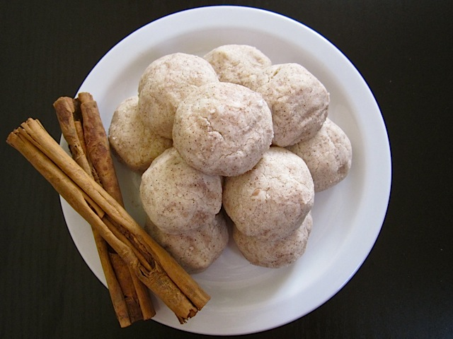 polvorones on white plate with cinnamon sticks on the side