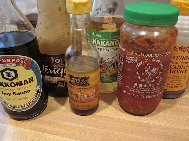 sauce ingredients (honey, soy sauce, rice vinegar, sesame oil, chili garlic paste and teriyaki sauce) bottles on counter