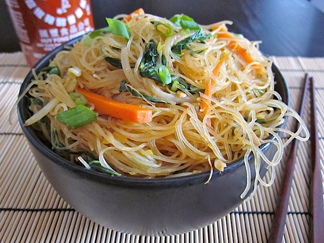Singapore Noodles, Rice Vermicelli in black bowl with chop sticks and a bottle of Sriracha on the side