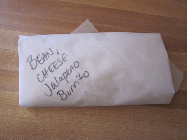 rolled burrito wrapped up with parchment paper and labeled
