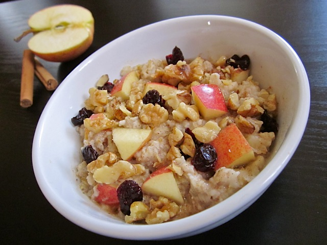autumn fruit and nut oatmeal in white bowl with cinnamon sticks and halved apple on the side