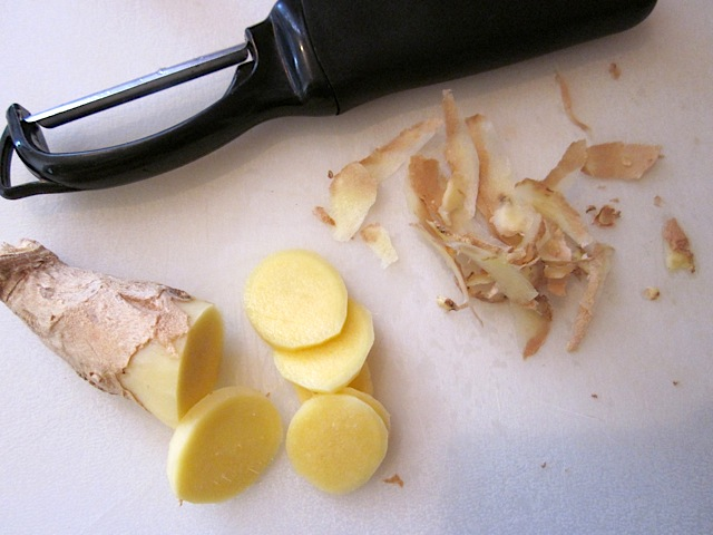 fresh ginger with peeler and sliced on counter