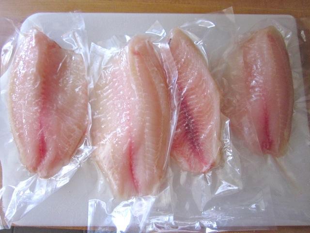 frozen tilapia filets in plastic packaging