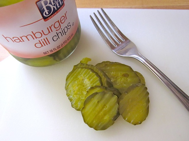 dill pickle slices with fork and jar of pickles in the background