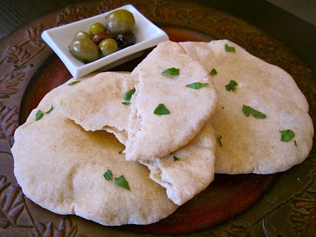 home made wheat pita with small bowl of olives on the side