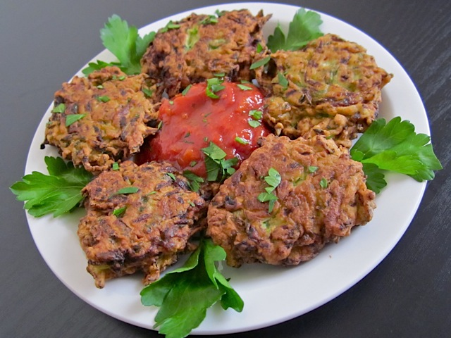 zucchini fritters plated on white plate with dipping sauce in middle and garnished with greens