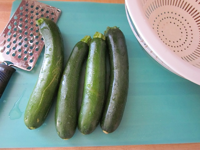 four zucchini with grater on the side