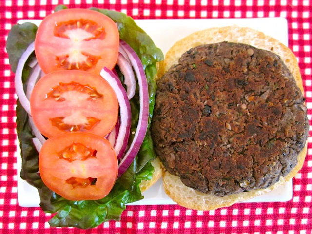Cooked Black Bean Burger on a bun with toppings on a plate, sitting on a red checked tablecloth