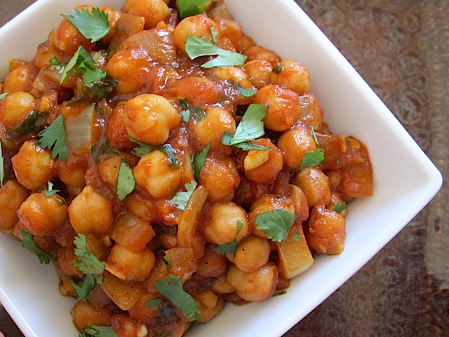 Curried Chick Peas in white bowl garnished with cilantro