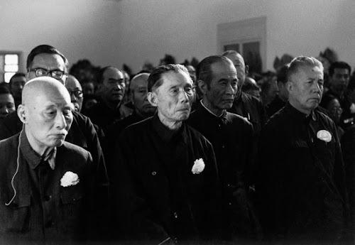 """""""文革""""结束不久,很多在此劫难中故去的文艺界人士得到平反,因此各地多有补开追悼会。1979年10月12日,叶圣陶、夏衍、周扬(左起)胸前佩戴着白花,情态肃然,在北京参加某场追悼会,远景的人丛中,隐隐约约有相声大师侯宝林的面容。.jpg"""