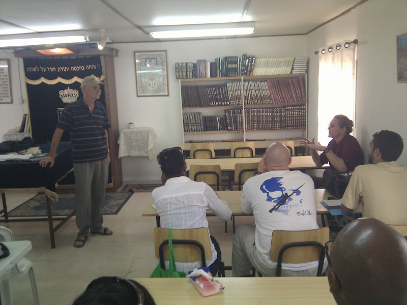Bruce Brill (left), with a visiting group in the Kfar Eldad Synagog.