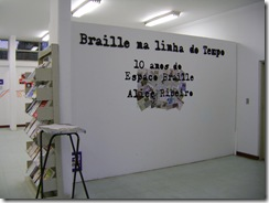 Entrada da biblioteca mostrando inscrição na parede- Braille na linha do tempo: 10 anos do Espaço Braille Alice Ribeiro