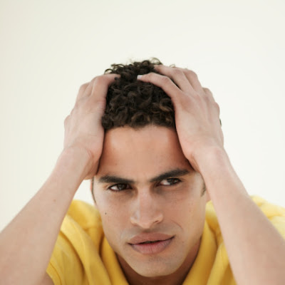 A worried, stressed man with his hands on his head.