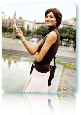 Woman smiling, standing and holding a cell phone.
