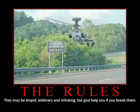 photo of an apache helicopter hovering behind a speed enforcement sign