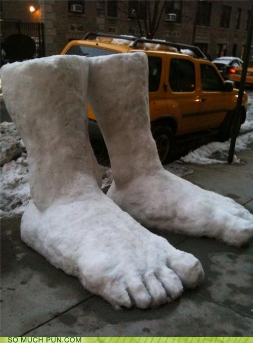 photo of two giant feet carved in the snow