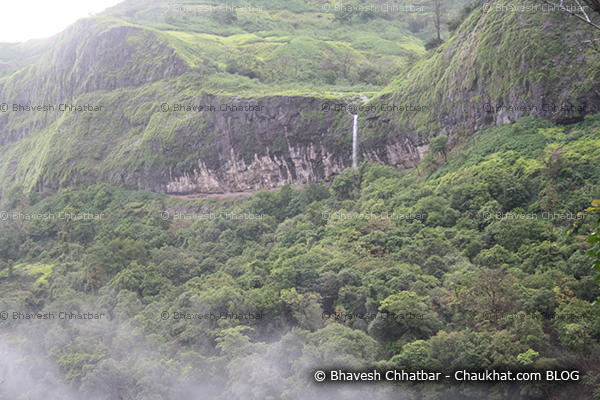 Huge mountain of Tamhini ghat with foliage, waterfall and clouds